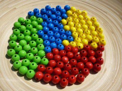 grüne, rote, blaue und gelbe Perlen liegen auf einem Teller.