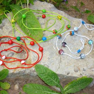 3 bunte Perlenketten liegen auf einem Stein